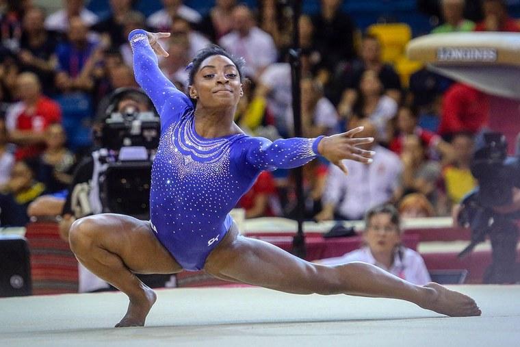 #PraCegoVer: Fotografia mostra a ginasta americana Simone Biles durante um movimento na prova de trave, durante os Jogos Olímpicos do Rio 2016.